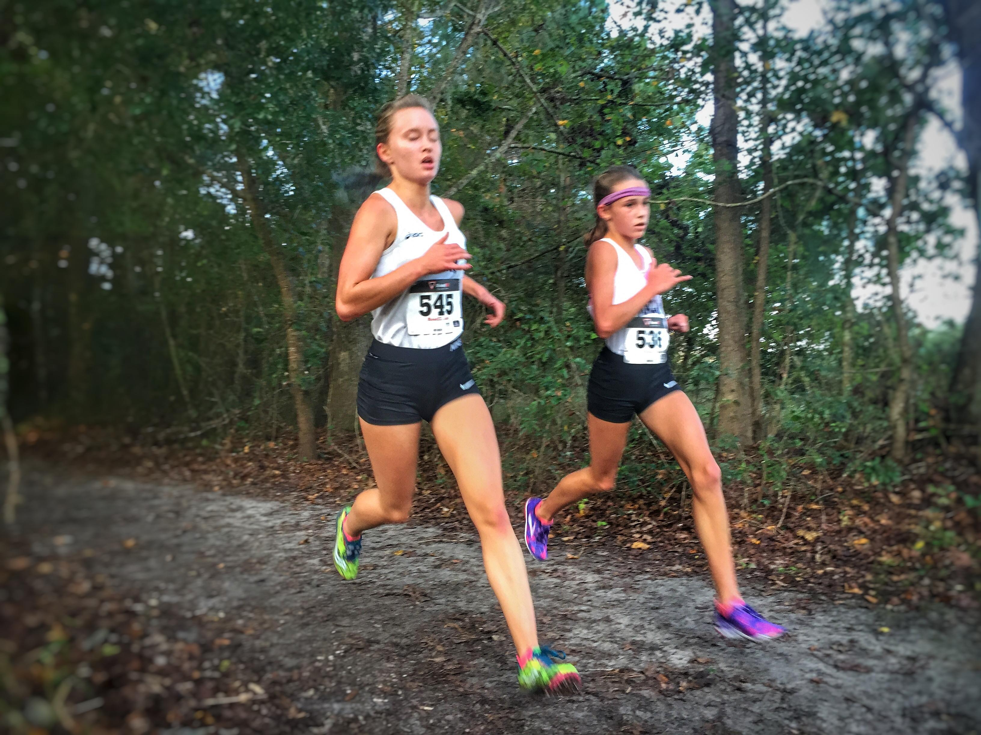 Maclay senior Caroline Willis (left) and seventh grader Lindsay James exit the woods past the mile mark of Saturday's Region 1-1A race at Alligator Lake in Lake City. James was third and Willis was fifth as the Marauders won a region title.