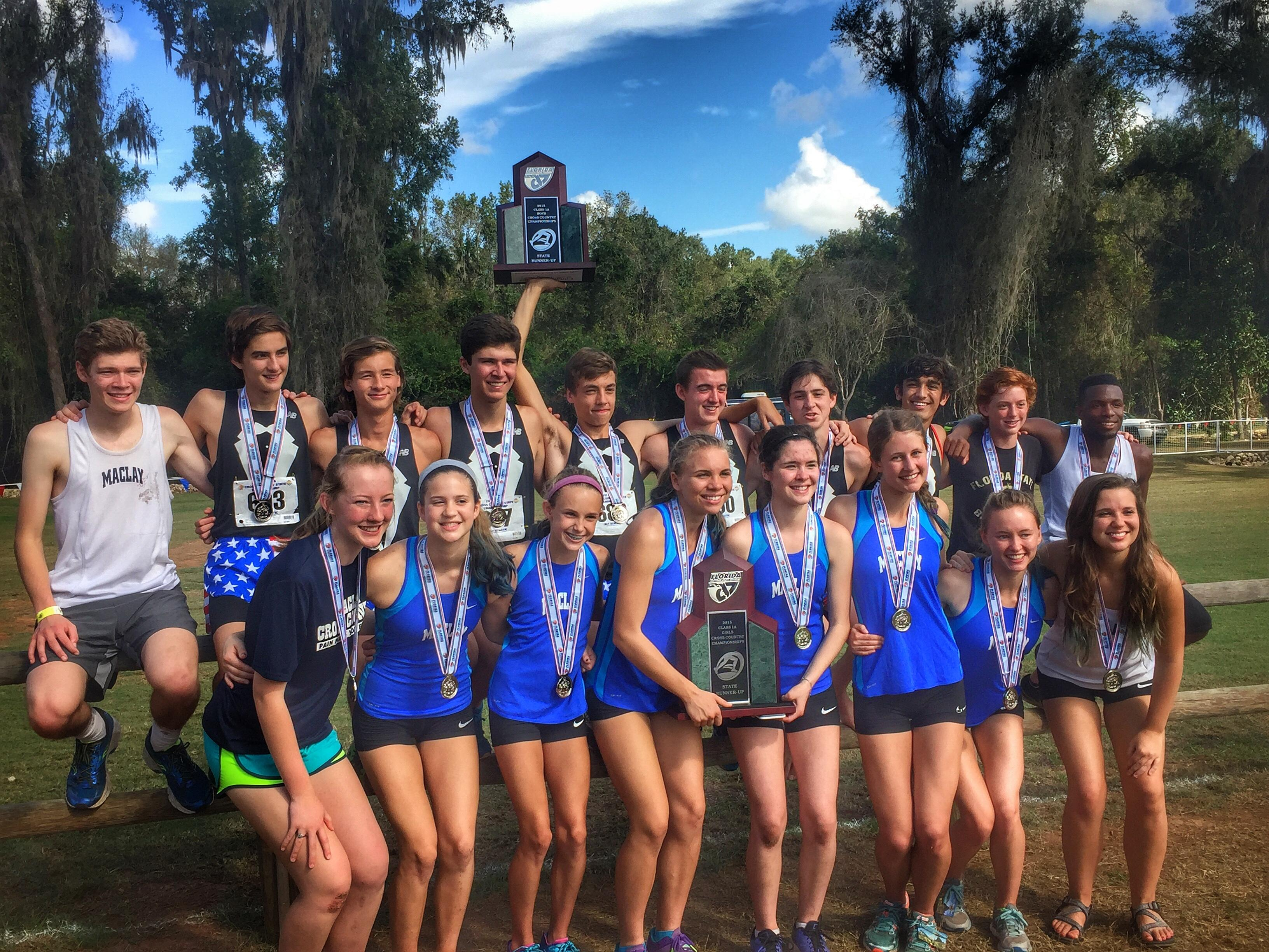 The Maclay boys and girls cross country teams celebrate Class 1A runner-up trophies for both groups following the conclusion of Saturday's FHSAA state cross country finals at Apalachee Regional Park.
