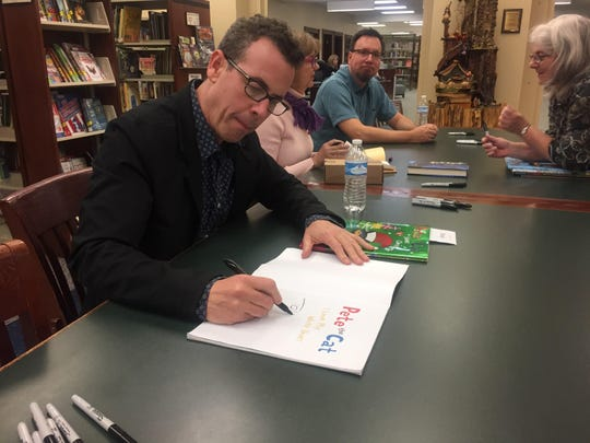 Author Eric Litwin signs a Pete the Cat book in the