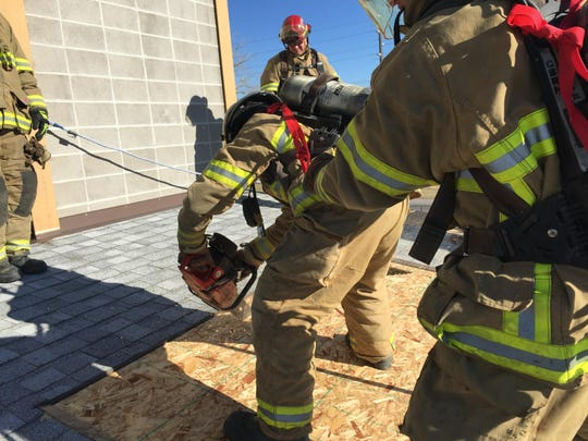 Rookies Bryan Martinez and Steven Luwe train on breaching a roof above a fire to vent smoke during training with Great Falls Fire/Rescue on Nov. 6.