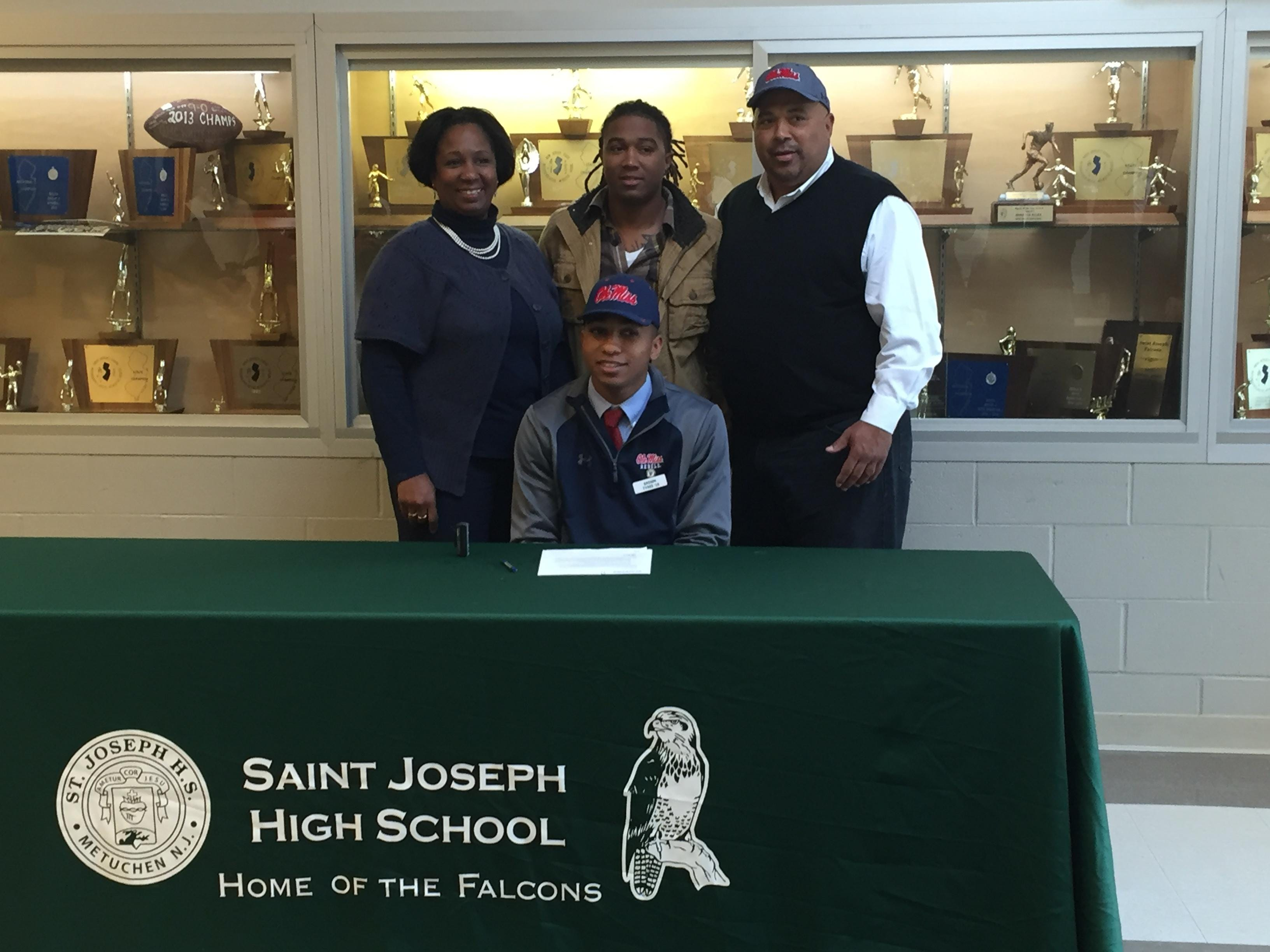 St. Joseph's Breein Tyree signs his National Letter of Intent to play basketball for the University of Mississippi surrounded by his family on Wednesday.