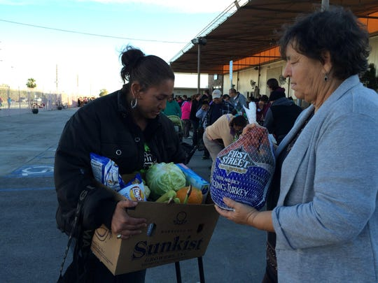 Gloria Gomez, Galilee Center co-founder, right, hands Linda Ortiz, 43, a turkey during Galilee Center's Thanksgiving Food baskets event Wednesday in Mecca.