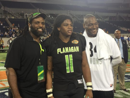 Devin Bush Sr., Devin Bush Jr. and Derrick Brooks pose for a photo after Flanagan High School won the Class 8A state championship at the Citrus Bowl Stadium on Saturday, Dec. 12, 2015.