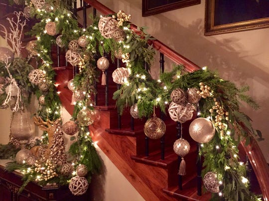 A bannister wrapped with fresh greenery and embellished with gold decorations.