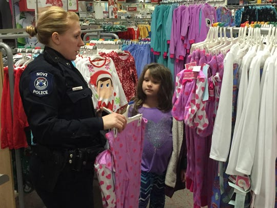 Officer Julie Warren keeps her eye out for some of Brooke Fitzpatrick's favorite colors during the Shop with a Hero program at Target.