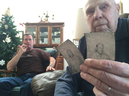 Ted Garnett shows a photo of himself in his World War II uniform while his son Brian listens to stories of his service.