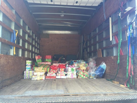 Gifts are loaded into the back of a truck, ready to be distributed to local boys and girls for Christmas.