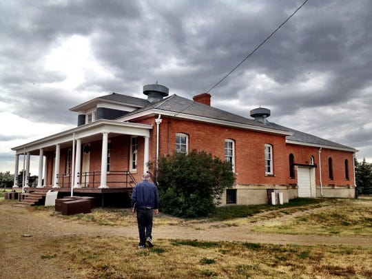 Wilson walks toward the Fort Assiniboine Guardhouse, which still has metal bars on the windows as it did when it housed prisoners.