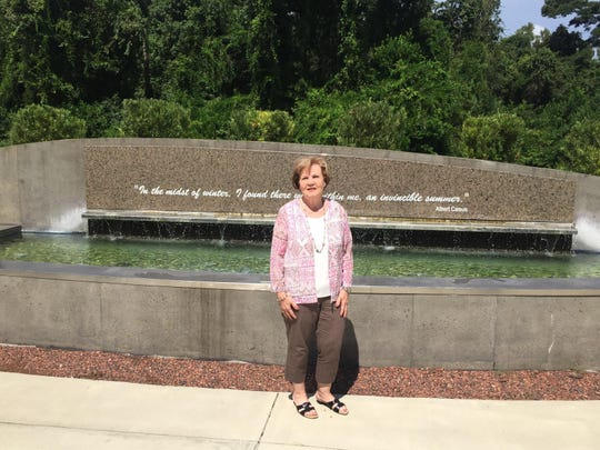Breast Cancer survivor Marie Roy by a fountain at TMH's Cancer Center