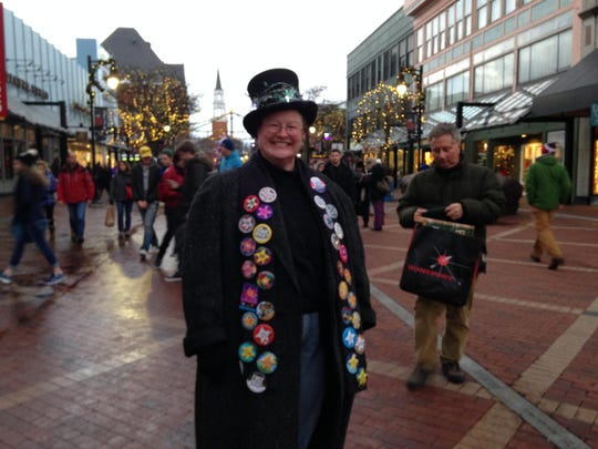 Pamela Gude of West Bolton sports a decorated top hat and a scarf with every First Night Burlington button from the past 33 years.