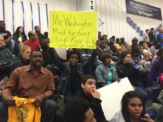 Nicole Moore holds a protest sign in support of former Attucks coach Phil Washington.