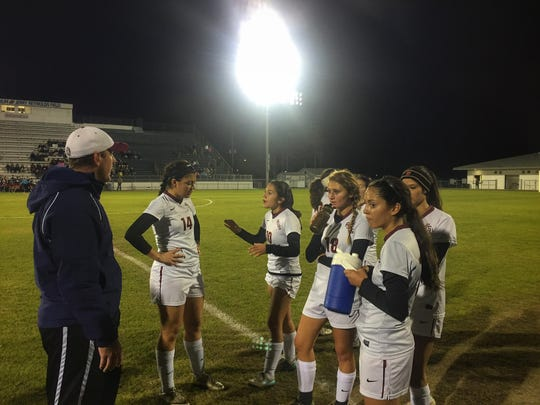 Florida High coach Kyle Crawford talks to his team during a first-half water break. The Seminoles topped Wakulla, 1-0, for their second consecutive district title.