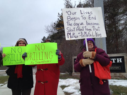 Jann Hoge, left, Tanisha Moir and Peggy Collins brave the cold to protest a proposal to drill for oil at a church in Southfield.
