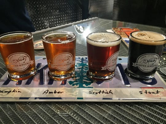 A flight of beer at the Busted Knuckle Brewery is served on an old license plate, in keeping with the brewery's mechanic theme.
