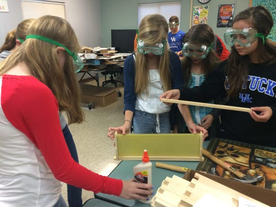 Students install wax into the bee hive frame.