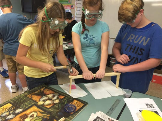 Students assemble the bee hive frame.