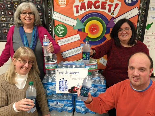 """A Camp Ernst Middle School class has launched its """"Trailblazers Providing Hope"""" campaign to collect and send bottled water to Flint, Michigan. Top row, from left: paraeducator Linda Campbell and teacher Susan Pastor-Richard. First row: social media coordinator Julie Pile and teacher Tim Roberts."""