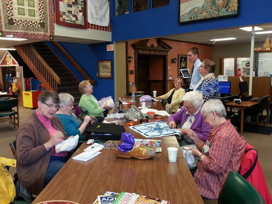 """With some of their quilts on display in the background, members of the Door County Quilters Guild work on quilting projects at the Sturgeon Bay branch of the Door County Library. The library hosts a """"Quilts Around the Library"""" show and meet-and-greet April 12."""