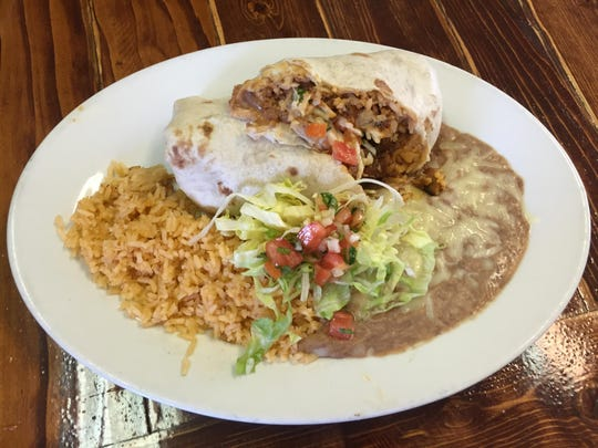 An al pastor burrito, one of several burritos at Albita's Mexican Restaurant, is stuffed and served with rice and beans.
