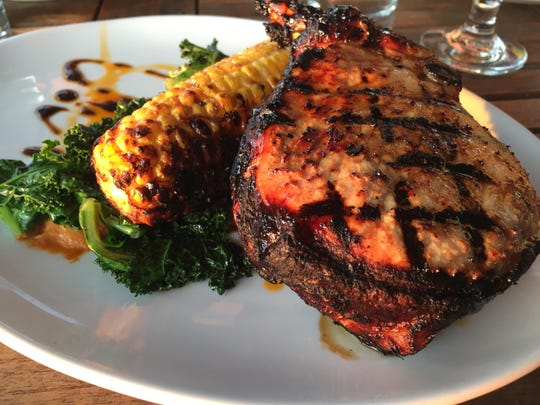 The grilled pork chop came atop Romesco sauce with a side of sauteed kale and grilled corn.