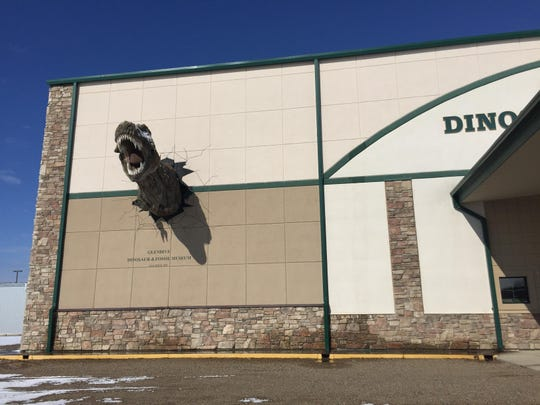 A dinosaur leaps from the side of the Glendive Dinosaur