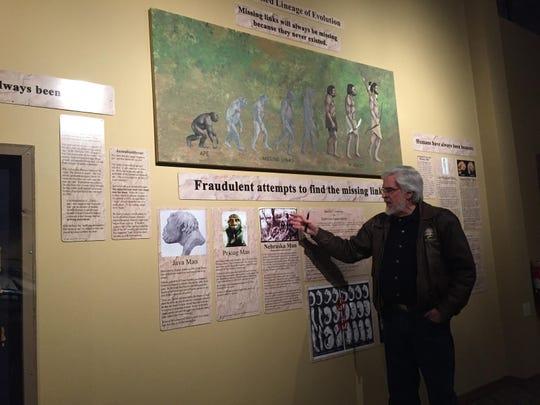 Museum director Otis Kline explains an exhibit in the Glendive Dinosaur & Fossil Museum that aims to refute the idea of human evolution.
