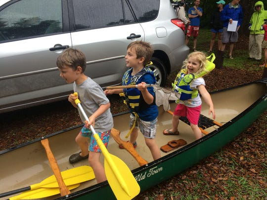 Leo Wiebler, Oscar Smart, and Lucy Smart get excited about an Earth Day canoe ride and trash cleanup.