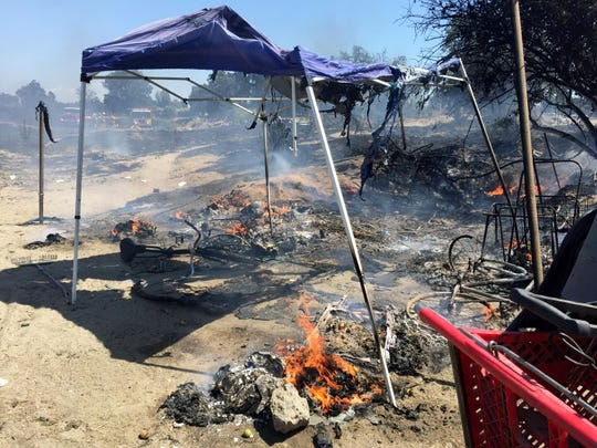 Flames still burn Saturday afternoon in campsite for homeless people on the north bank of the St. Johns River, just north of Visalia, after a fire burned through part of the campsite.