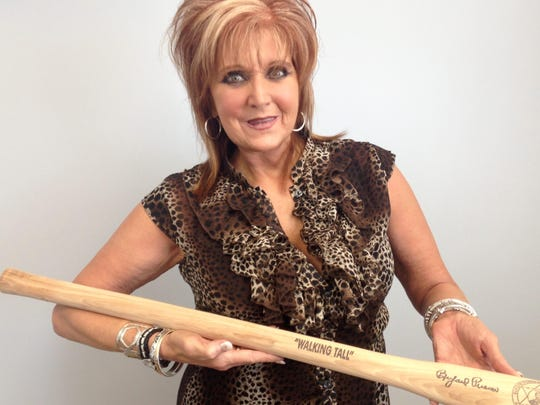 Buford Pusser's daughter, Dwana Pusser, shows a replica of Buford's stick.
