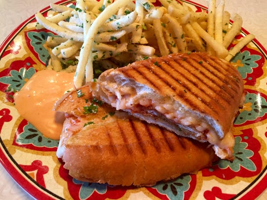 A chicken Parmesan panino — a twist on the chicken Parm grinders of the Northeast — comes with fries and sriracha rémoulade at Toni Rigatonis.