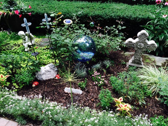 This memorial garden, in honor of Donna Comer's parents, is one of many components of her extensive backyard garden in Farmington Hills.