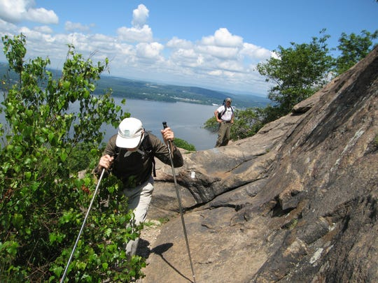 The Hudson River provides the background as local hikers scale popular Breakneck Ridge in Hudson Highlands State Park.