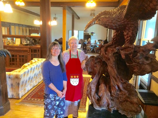 General manager Kerri Kumasaka and co-owner Anne Wilson Schaef stand by a large wood eagle that graces the entrance of the Peace Valley Hot Springs outside of Boulder.