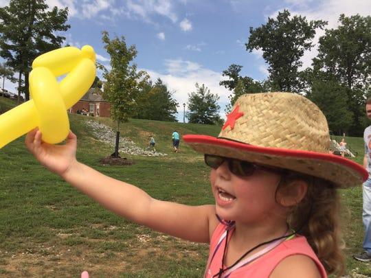 Starlit Ledyard, 4, of Monfort Heights, Ohio, waves a balloon animal in the air as she runs to show her mother in Tower Park in Fort Thomas during Campbell County Public Library's World's Largest Storytime as part of The Enquirer's 175th anniversary celebrations to promote literacy.