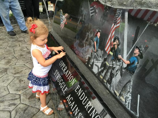 Anna Belle France, 2, of Latonia, views the base of the Northern Kentucky 9/11 Memorial before its dedication ceremony Sept. 11, 2015.