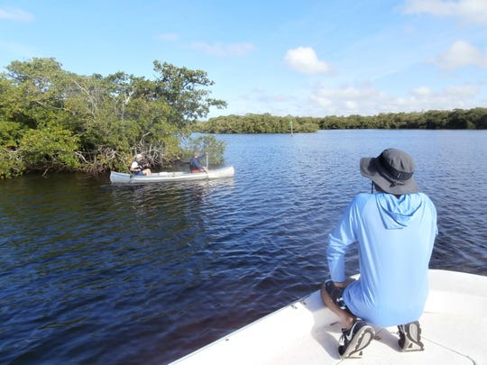 FGCU Associate Professor Hidetoshi Urakawa checks with students in a canoe collecting Crown Conch snails during a recent class.