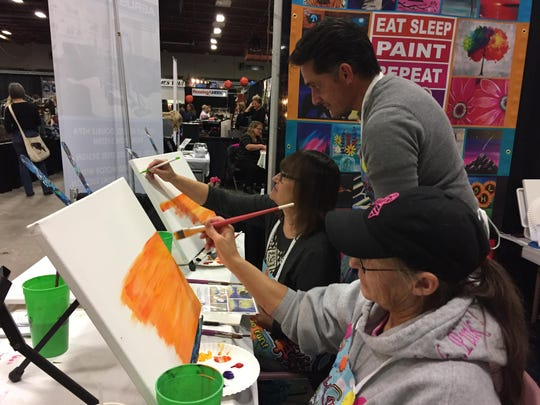 With a some help from volunteer Jason Newman, the Brush Crazy Booth at What Women Want gave sisters Susan Stevens, left, and Linda Rooney a chance for a little friendly competition.