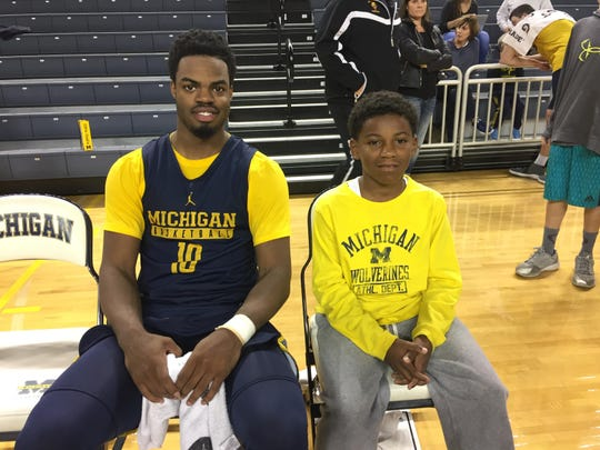 Michigan guard Derrick Walton Jr. takes a picture with fan Ashton Watson, 10, at Tuesday's third annual open practice and selfie night at Crisler Center.