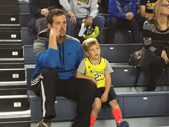 Michigan fan Nathan Konrad brought his son, Clayton, to Crisler Center for Tuesday's third annual open practice and selfie night for the men's basketball team.