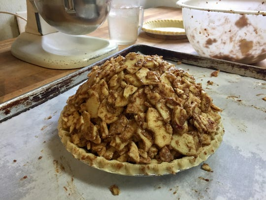 A mile-high apple pie, one of five pies offered at Homage Bakery for the 2016 holidays, awaits its top crust. The apple pies contain about 4 pounds of Braeburn fruit.