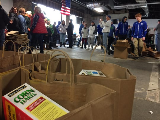"Volunteers gather inside a warehouse in Newport Friday to bag $25,000 in groceries for charity Big Stef's 30th and final Christmas gift to families in need. Big Stef Inc., a nonprofit, is disbanding due to the death of founder Robert ""Big Stef"" Steffen in May."