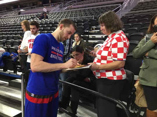 76ers guard and former Michigan star Nik Stauskas signs an autograph for Jeanna Cooper of Warren before Monday's game against the Pistons at the Palace. He scored four points in the 76ers' 113-96 loss.