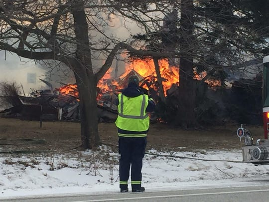 An emergency worker at the scene of a fire Thursday that closed U.S. 2 in South Hero.