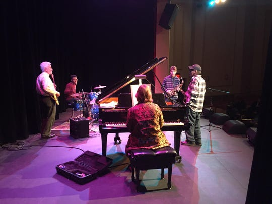 Harry E. Spencer Jr. with members of his ensemble and students in the baby grand for an Arts Academy showcase.