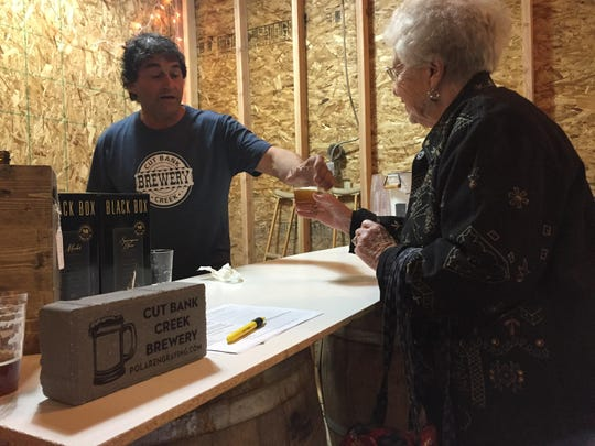 Louis Stoltz pours Penguin Piss Amber at a sneak peak Friday of Cut Bank Creek Brewery. The brewery is selling engraved bricks, left, to help launch the business.
