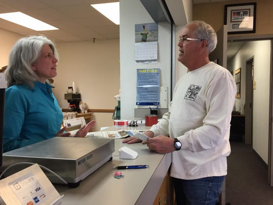 Gary Splittberger tells Sharon McCrea, postmaster for the post office on Malmstrom Air Force Base, that her post office is his 312th and final post office to visit in Montana.
