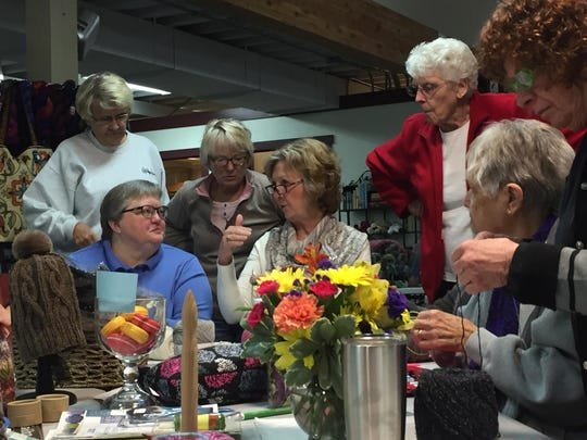 Pam Jensen, center, gives pointers to the Thursday knitting group at Pam's Knit 'n' Stitch. Jensen has retired after 25 years of owning the business.