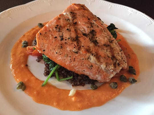 Grilled salmon is served with oven-dried tomato, wilted spinach, crispy capers, toasted quinoa and roasted pepper sauce at the Grand Union Hotel's restaurant.