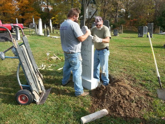 Workmen install new headstones