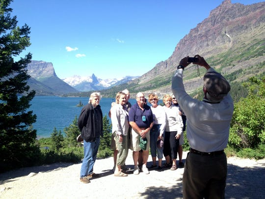 Glacier National Park Jammer Eric Kendall takes a photo of a group of tourists from Illinois. The state reported 12 million tourists visited Montana last year.